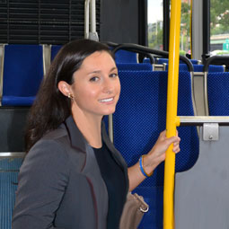 A picture of a young woman in a suit holding the safety pole on a DC area bus